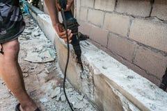 Plancher en béton de ciment de perçage d'homme de travailleur avec la machine photos libres de droits