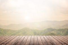Plancher en bois avec le fond brouillé par paysage de montagne Photo stock