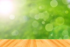 Plancher en bois et fond vert abstrait de bokeh Photographie stock libre de droits