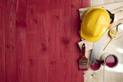 Plancher en bois rouge avec une brosse, une peinture, des outils et un casque Photographie stock libre de droits
