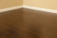 Plancher et plinthes nouvellement installés de stratifié de Brown dans la maison Photos stock