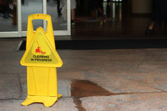 Plancher humide de précaution devant la porte de bâtiment Photographie stock libre de droits