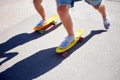 Planches à roulettes adolescentes d'équitation de couples sur la route urbaine Images libres de droits