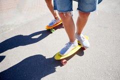 Planches à roulettes adolescentes d'équitation de couples sur la route urbaine Image libre de droits