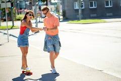 Planches à roulettes adolescentes d'équitation de couples sur la rue de ville Image stock
