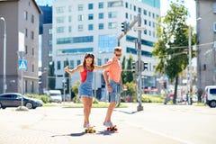 Planches à roulettes adolescentes d'équitation de couples sur la rue de ville Images stock