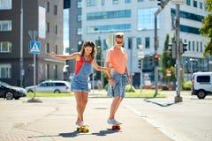 Planches à roulettes adolescentes d'équitation de couples sur la rue de ville Photo libre de droits