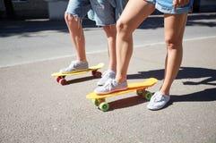 Planches à roulettes adolescentes d'équitation de couples sur la rue de ville Image libre de droits