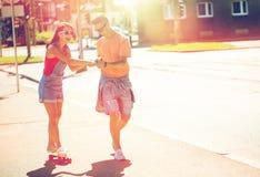 Planches à roulettes adolescentes d'équitation de couples sur la rue de ville Photo stock