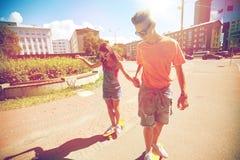 Planches à roulettes adolescentes d'équitation de couples sur la rue de ville Photos stock