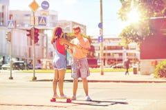 Planches à roulettes adolescentes d'équitation de couples sur la rue de ville Photographie stock