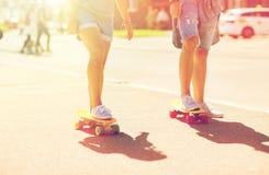 Planches à roulettes adolescentes d'équitation de couples sur la rue de ville Images libres de droits