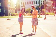 Planches à roulettes adolescentes d'équitation de couples sur la rue de ville Photographie stock libre de droits