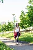 Planches ? roulettes de monte de fille sportive sur la rue Dehors, mode de vie urbain photos stock