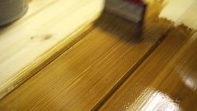 Planches en bois de peinture avec de l'huile protectrice de couleur brune banque de vidéos