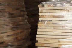 Planches en bois empilées dans les rangées enveloppées dans l'aluminium en plastique photographie stock