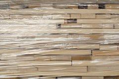 Planches en bois empilées dans les rangées enveloppées dans l'aluminium en plastique photos libres de droits