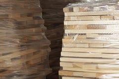 Planches en bois empilées dans les rangées enveloppées dans l'aluminium en plastique photographie stock libre de droits