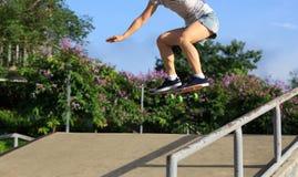 Planchiste de femme faisant de la planche à roulettes au skatepark Image stock