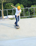 Planchiste de jeune femme faisant de la planche à roulettes au skatepark Photos libres de droits