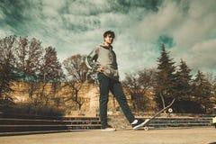 Planchiste de type montant une planche à roulettes sur un skatepark Le jeune homme sautant avec une planche à roulettes photographie stock libre de droits