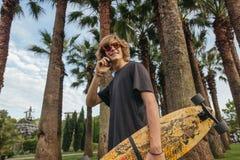 Planchiste marchant avec le longboard à disposition et le téléphone parlant photographie stock