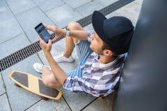 Planchiste masculin habile dedans en ligne par le téléphone photo stock