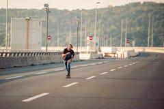 Planchiste montant un patin au-dessus d'un pont en route urbaine Tour gratuit s images libres de droits