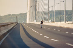 Planchiste montant un patin au-dessus d'un pont en route urbaine Tour gratuit s photo libre de droits