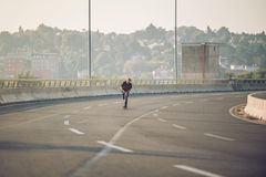 Planchiste montant un patin au-dessus d'un pont en route urbaine Tour gratuit s image stock