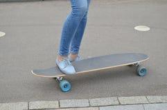 Planchiste, pieds femelles faisants de la planche à roulettes dans le skatepark Photo stock