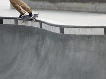 Planchiste rectifiant un rail au bord d'une piscine de cuvette à un parc de patin photo stock