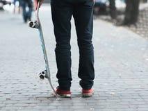 Planchiste tenant le patin à la rue Images libres de droits
