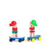 Planchistes de pince à linge dans casquettes de baseball Homme et femme sur les panneaux bleus de patin Fond blanc, l'espace de c Photo stock