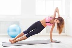 Plancia della donna di forma fisica che si prepara all'interno Immagine Stock