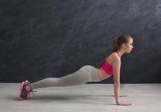 Plancia di addestramento della donna di forma fisica a fondo grigio all'interno Fotografia Stock Libera da Diritti