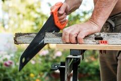 Plancia di lavoro di taglio dell'uomo caucasico con la sega a mano all'aperto di estate Fotografia Stock