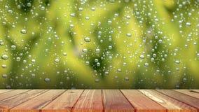 Plancia di legno con goccia di acqua astratta su fondo di vetro del negozio di finestra di vetro un giorno piovoso immagine stock