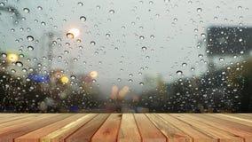 Plancia di legno con goccia di acqua astratta su fondo di vetro del negozio di finestra di vetro un giorno piovoso fotografie stock