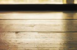 Plancia di legno della tavola di fronte alla finestra con luce solare immagine stock libera da diritti