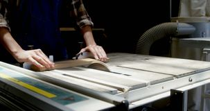 Plancia di legno di taglio del carpentiere sulla macchina di legno 4k della sega stock footage