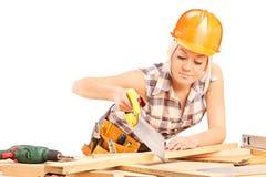 Plancia femminile di taglio del carpentiere con una sega a mano Fotografia Stock