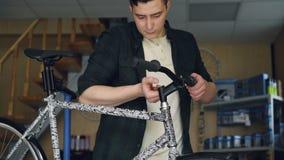 Plandeka strzał młodego człowieka roweru repairman naprawianie łamający handlebar nowożytny bicyle z narzędziami Naprawiać cykle, zbiory