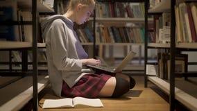 Plandeka w górę strzału dziewczyna w czerwonym spódnicowym obsiadaniu na podłodze w bibliotece zbiory wideo