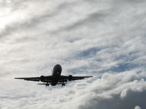 Plane 2. Landing plane silhouette on a cloudy day Royalty Free Stock Photo