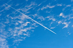 The plane. Flies in the blue sky on a background of white clouds, leaving a strip of Stock Images