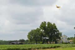 Plane Above Farmhouse. A yellow cropdusting plane flies near the clouds above the field of trees of a rural southern country farmhouse Royalty Free Stock Images
