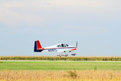 Plane above runway after lift off. Personal airplane in air just after lift off. Runway visible and cornfield in background stock photography