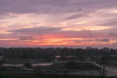Plane against orange and purple sky at sunset, with misty mounds of earth and buildings against trees. View of plane against orange and purple sky at sunset royalty free stock photos