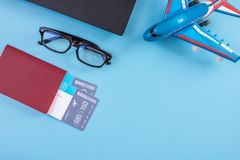 Plane, air tickets, passport, glasses and phone with headphones on a blue background. Concept of preparing for travel. Plane, air tickets, passport, glasses and stock photo